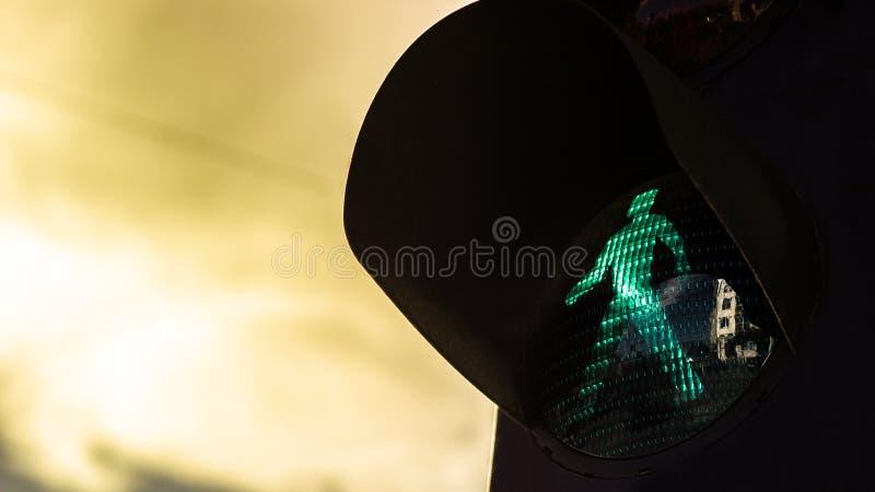 Зеленый пешеходный свет на драматическом небе стоковое фото rf