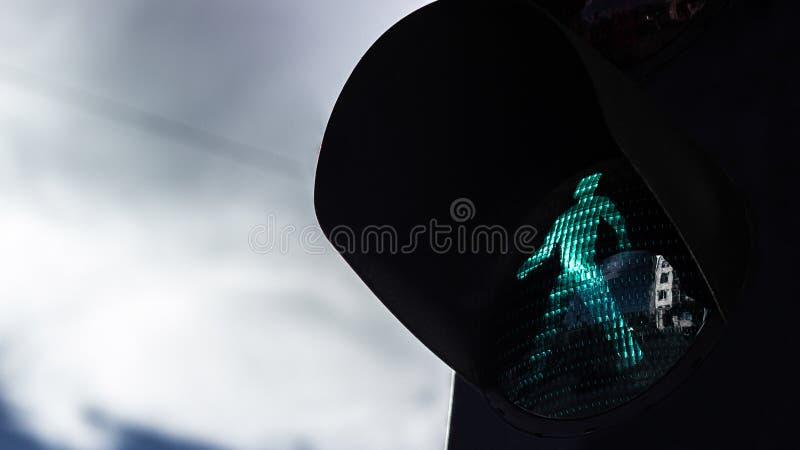 Зеленый пешеходный свет на драматическом небе стоковое фото