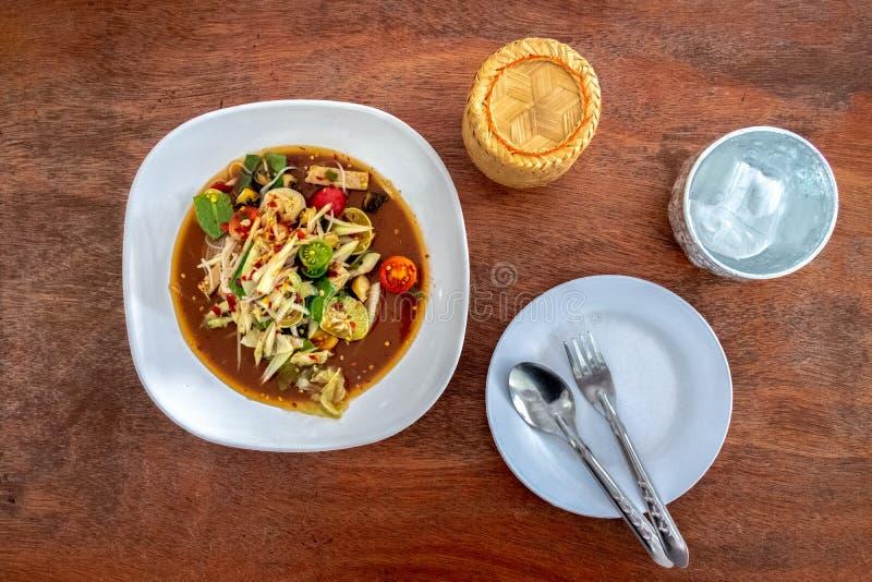 Зеленый салат папапайи в белой плите и липком рисе на деревянной предпосылке стоковое фото