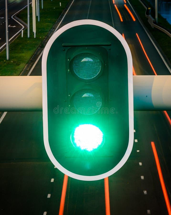 Зеленый светофор с пустым шоссе на предпосылке, концепции для идти вперед, позитивность, успех стоковое изображение rf