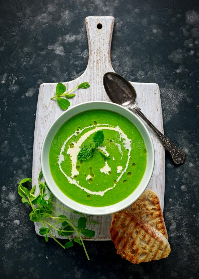 Зеленый сладостного суп гороха и мяты с моросью сливк и оливкового масла служил с зажаренными здравицами ciabatta стоковая фотография rf