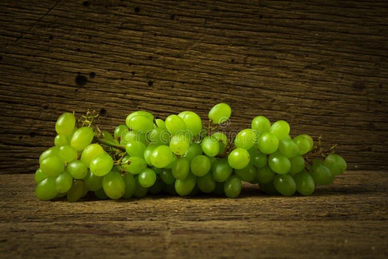 зеленый цвет виноградин на старой древесине стоковые фотографии rf