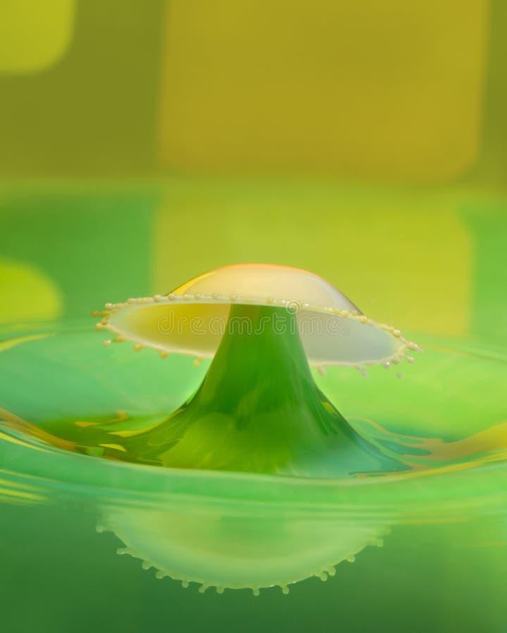 Зеленый цвет и искусство падения воды золота созданное с отражением стоковое изображение