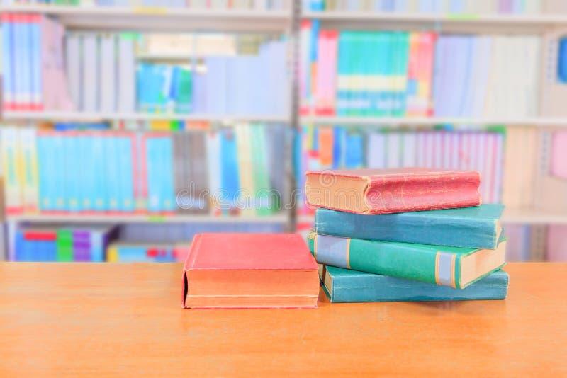 Зеленый цвет старой книги красно- куча внутренняя школа библиотеки на деревянном столе и расплывчатая предпосылка книжных полок стоковое изображение rf