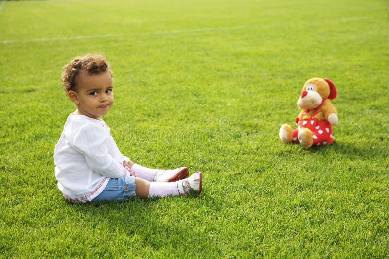 зеленый цвет травы девушки младенца милый ее сидя t стоковая фотография