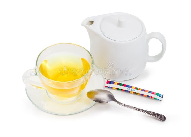Зеленый чай в стеклянной чашке на поддоннике, ложке чая, чайнике стоковое изображение
