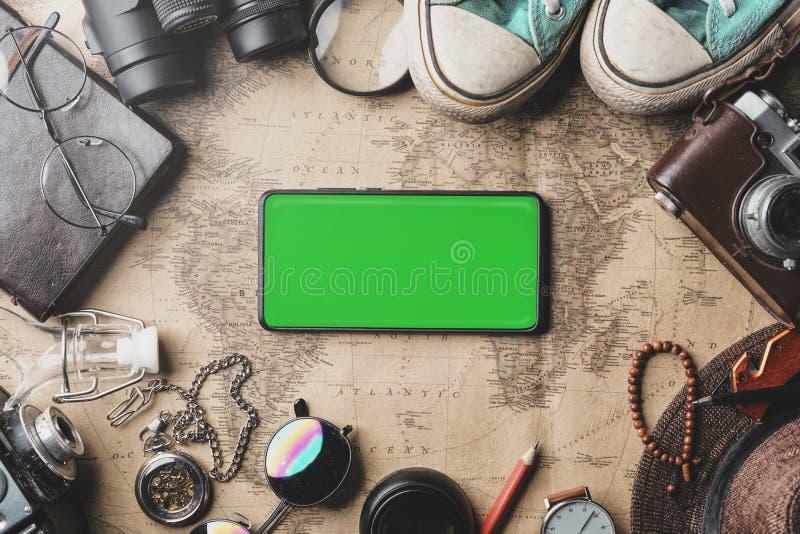 Зеленый экран на смартфоне, предпосылке концепции перемещения Надземный взгляд аксессуаров путешественника на старой винтажной ка стоковое фото