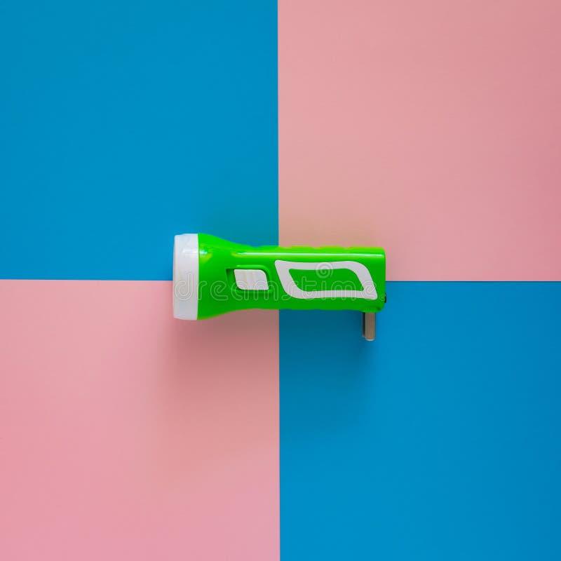 Зеленый электрофонарь на пинке и голубой бумаге стоковое фото