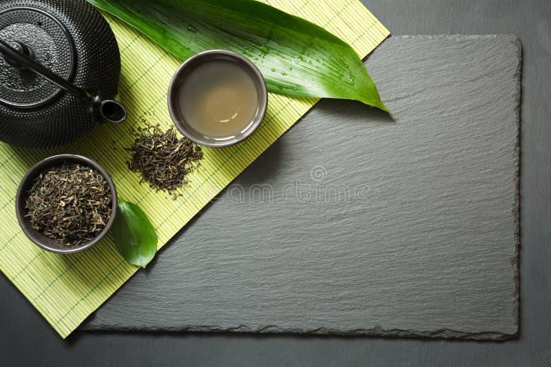 Зеленый японский чай на черной предпосылке шифера Черные чайник и шар с зеленым чаем Взгляд сверху с космосом экземпляра стоковые изображения