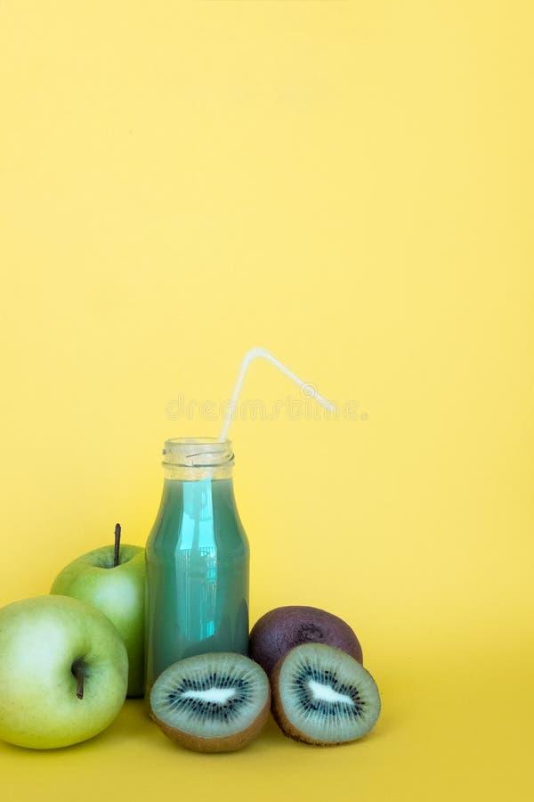 Зеленый smoothie в бутылке и ингредиентах Естественный, органический здоровый сок на желтой предпосылке с космосом экземпляра стоковая фотография rf
