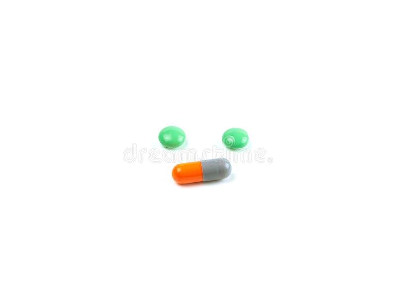 Зелёные таблетки и капсулы оранжевого цвета выделяют белый фон, лекарс стоковая фотография rf