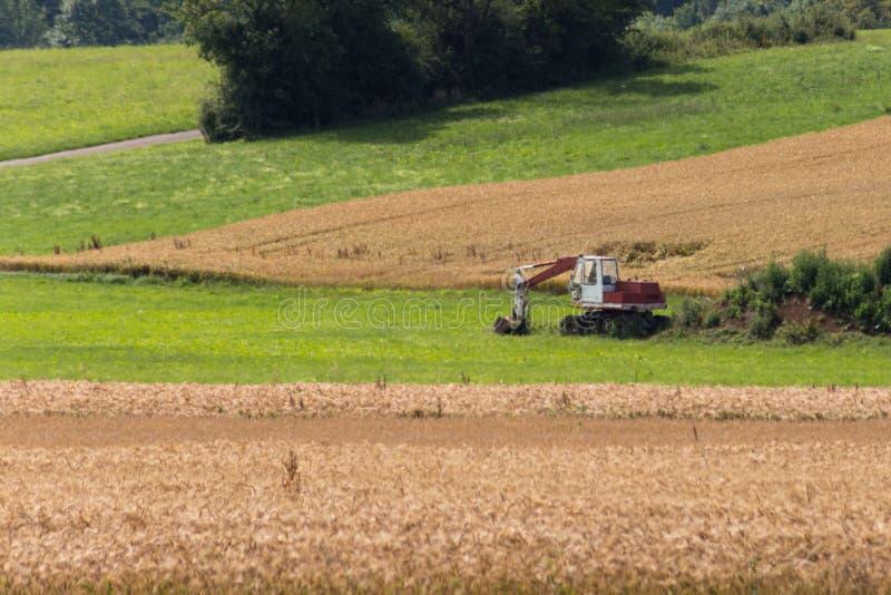 Землекоп с хатой и земля на ландшафте кукурузного поля сельском стоковые фото