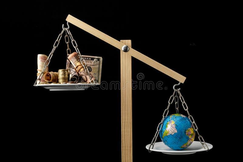 Земля и деньги на балансе 2 лотков стоковая фотография