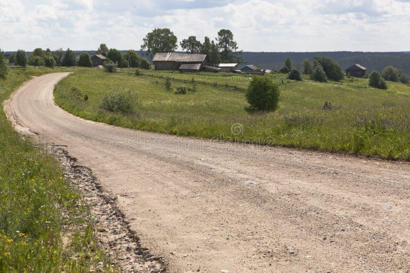 Земная дорога идя к деревне Взгляд деревни Markovskaya, зоны Vologda района Verhovazhsky стоковое изображение