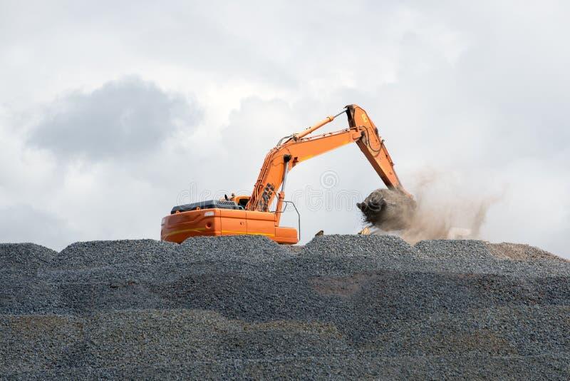 Землекоп собирая камень для дорожного строительства стоковые изображения
