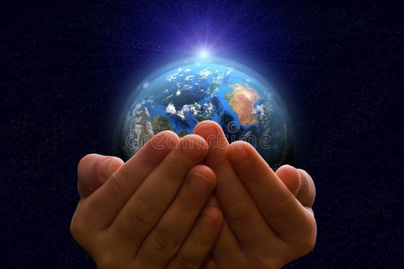 Земля планеты в руках ребенка стоковые фото
