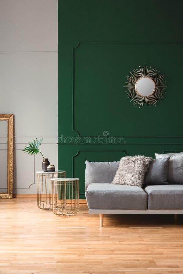 Зеркало формы Солнца на пустой зеленой стене в стильном интерьере живущей комнаты стоковое фото
