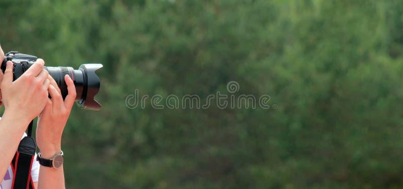 Зеркальная камера в мужских руках Парень с наручными часами фотографирует что-то на зеленой абстрактной предпосылке овоща _ стоковая фотография rf