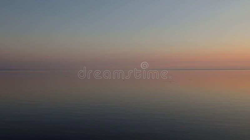 Зеркальноподобное море после захода солнца стоковое фото
