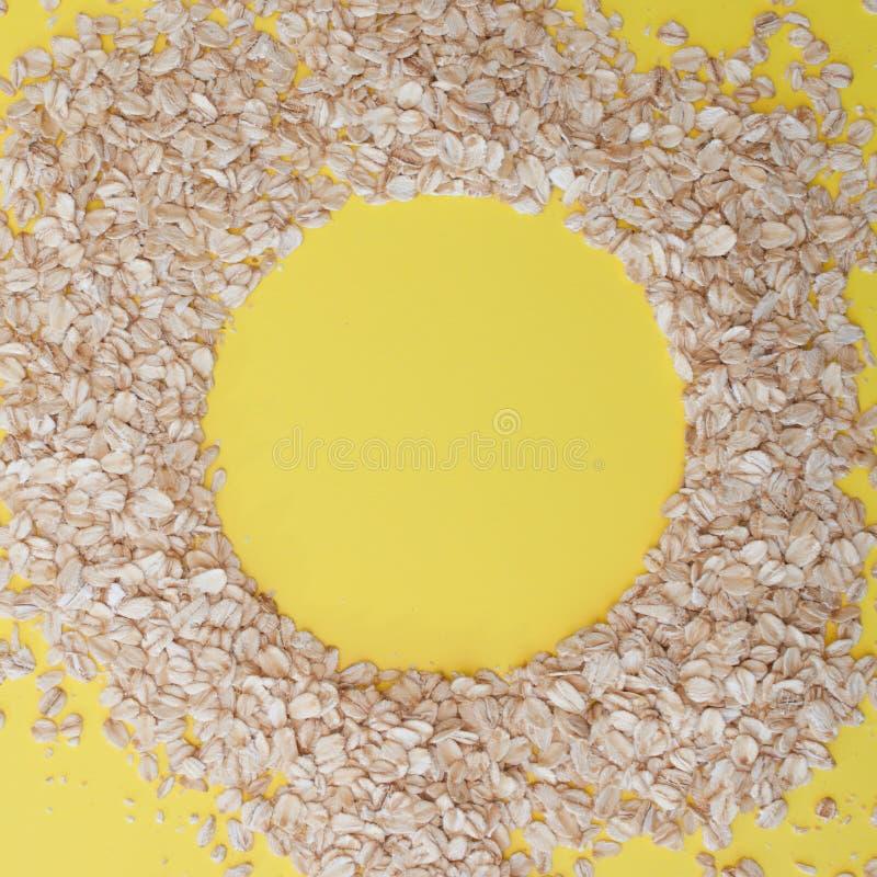 Зерна овсяной каши на желтой предпосылке, космосе экземпляра Хлопья овса лежат в форме круга стоковые изображения rf