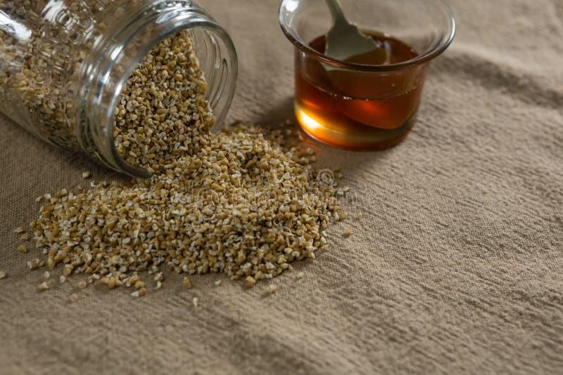 Зерна разливая из опарника с шаром меда стоковые фото