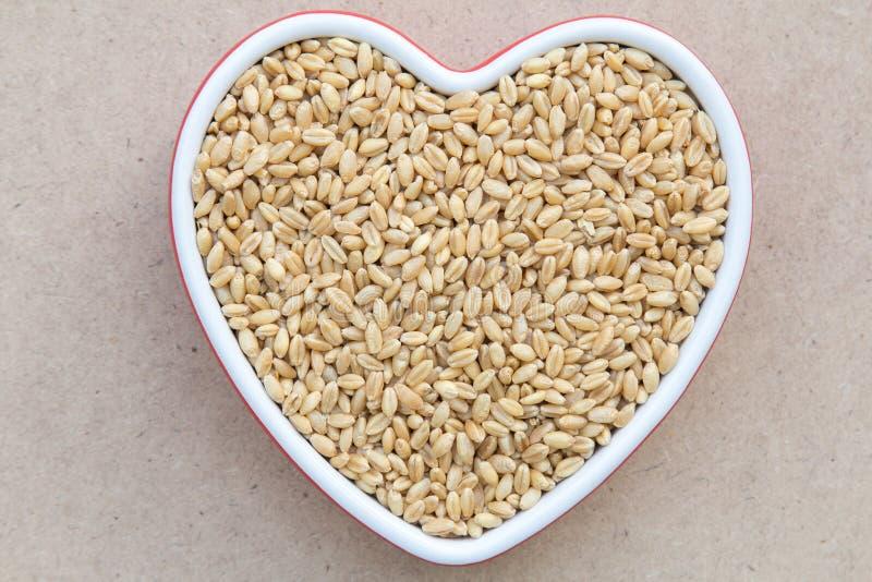 Зерно пшеницы в блюде фарфора сердца форменном стоковые фото