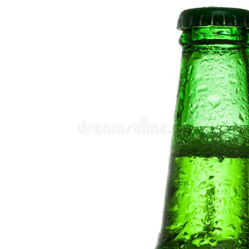 Зеленая пивная бутылка с водой падает над белой предпосылкой - близкой поднимающей вверх съемкой студии стоковое фото