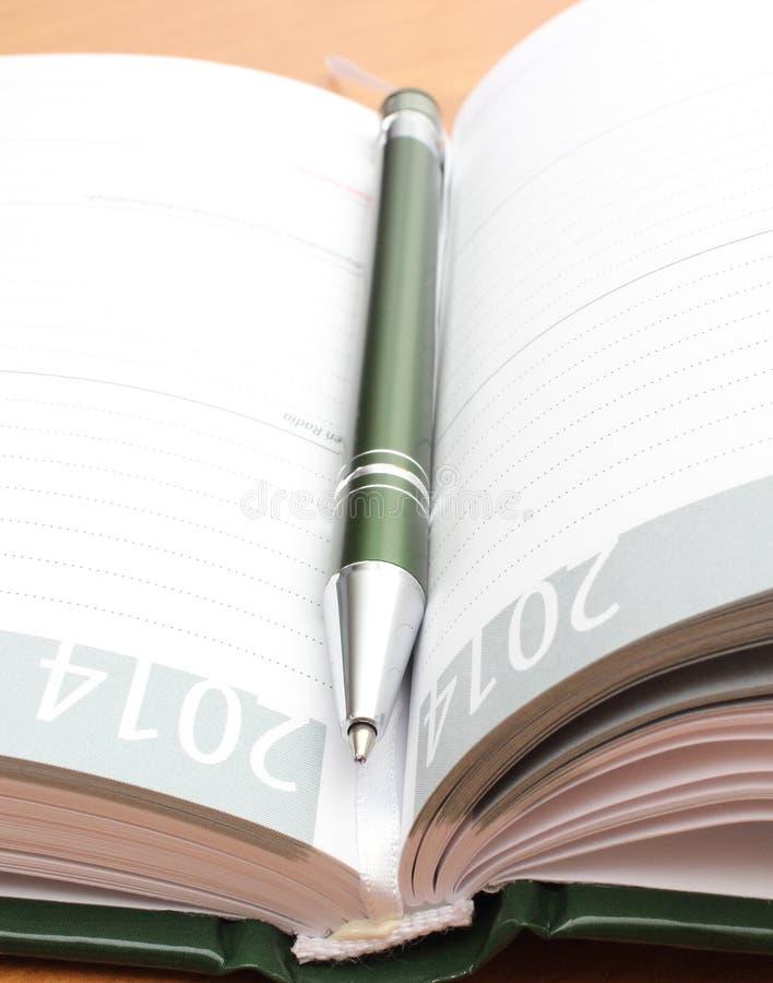 Зеленая ручка лежа на открытом организаторе на столе стоковые фото