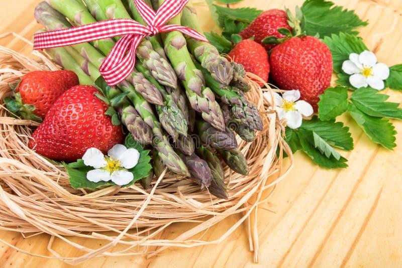 Зеленая спаржа с свежей клубникой на яркой деревянной предпосылке стоковая фотография