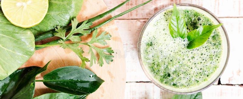 Зеленое травяное питье вытрезвителя с ингридиентами на разделочной доске стоковое фото
