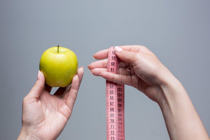Зеленое яблоко в женских руках на серой предпосылке Потеря веса, диета стоковые изображения