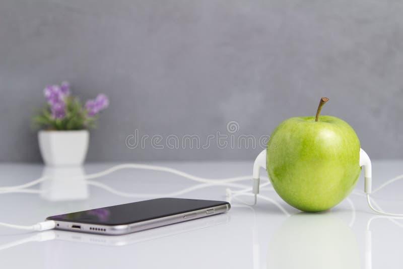 Зеленое Яблоко при шлемофон соединенный к телефону стоковое изображение rf