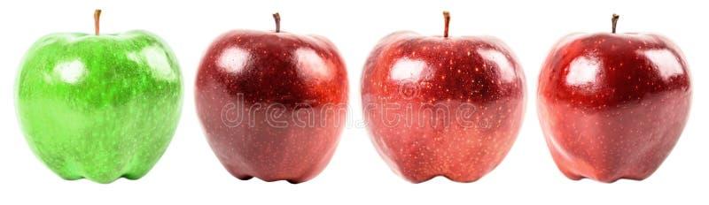 Зеленое яблоко среди красных яблок стоковые фото