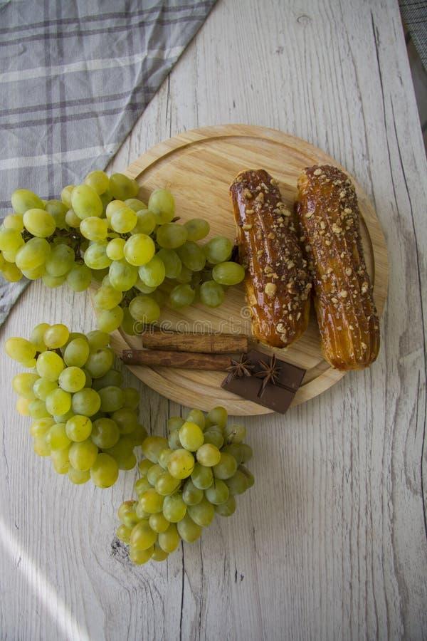 Зеленые виноградины и eclairs карамельки стоковая фотография