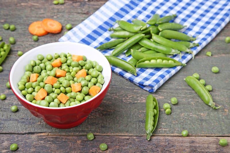 Зеленые горохи и моркови стоковые изображения