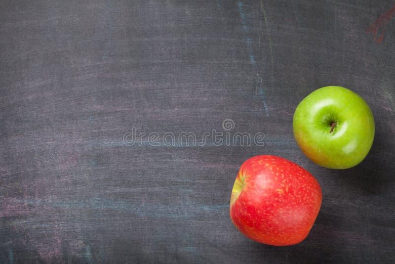 Зеленые и красные яблоки на предпосылке классн классного или доски стоковые изображения rf