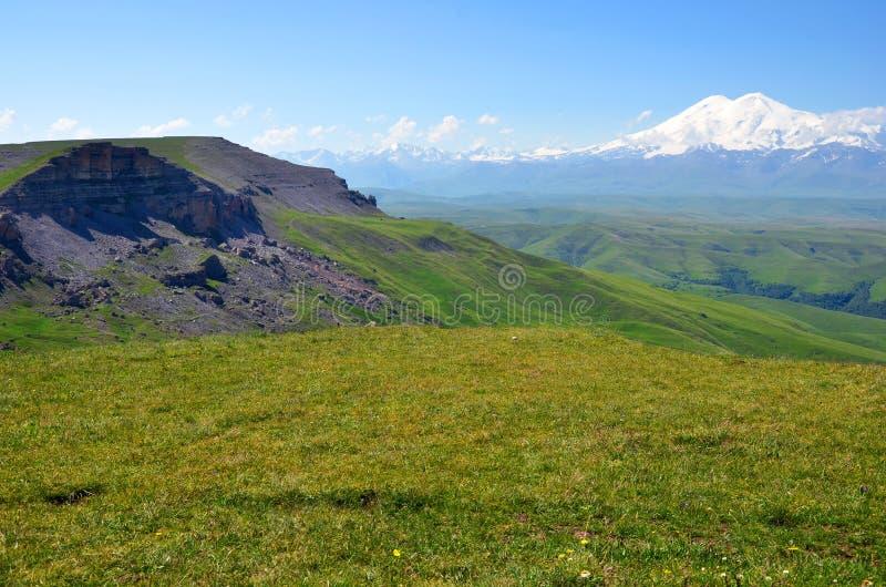 Зеленые поля и скалы на предпосылке горы стоковые фотографии rf