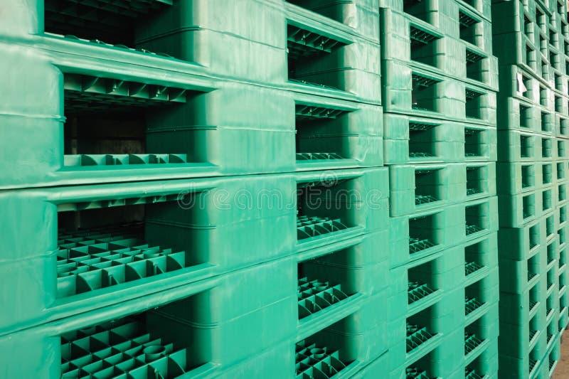 Зеленые пластичные паллеты в складе стоковая фотография