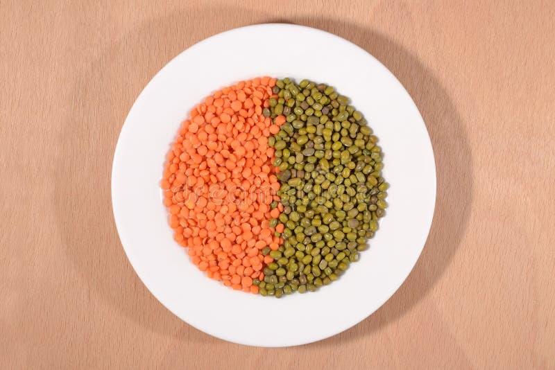 Зеленые фасоли mung и красная сырцовая чечевица на белой плите стоковая фотография rf