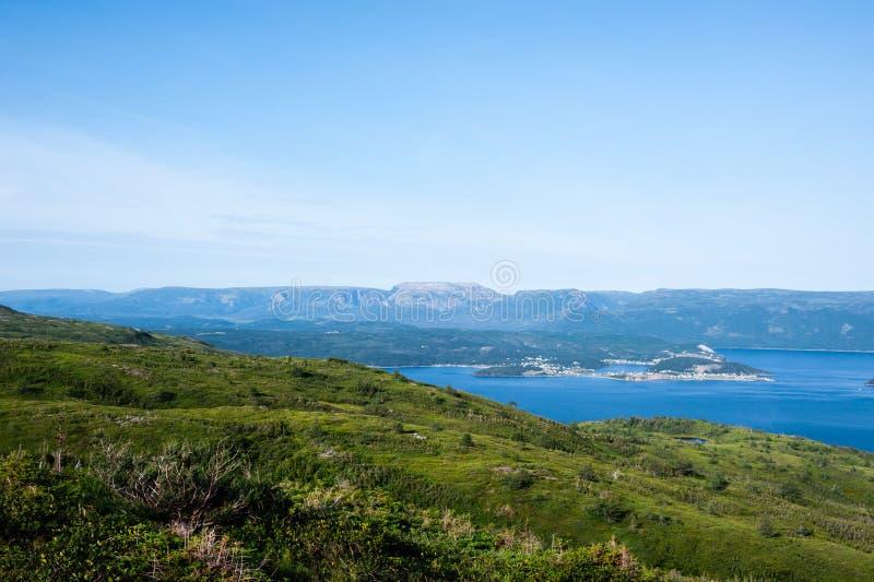 Зеленые холмы приближают к воде против плато под бледным - голубое небо стоковое фото rf