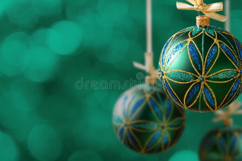 Зеленые шарики рождества вися на абстрактной предпосылке стоковые изображения