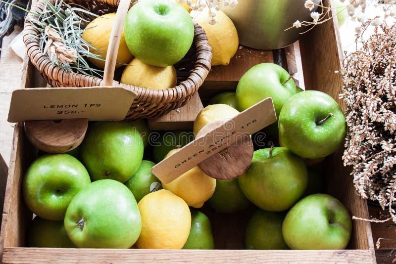 Зеленые яблоки и желтые лимоны в деревянной коробке стоковое фото rf