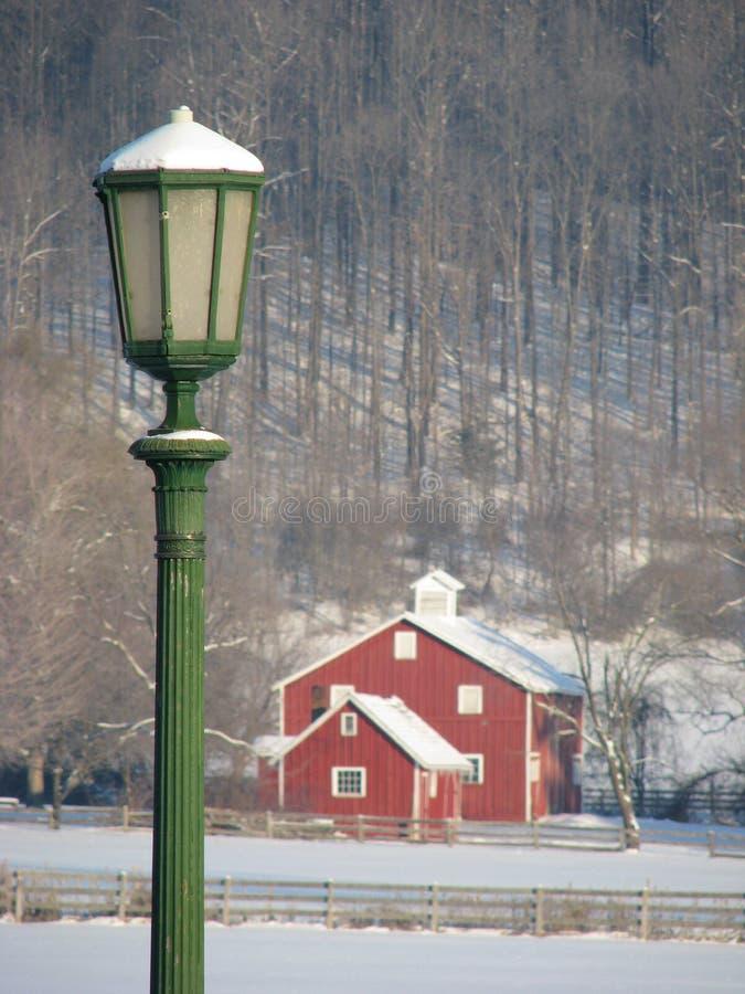 Зеленый столб лампы и красный амбар предусматриванные в снеге стоковые фотографии rf