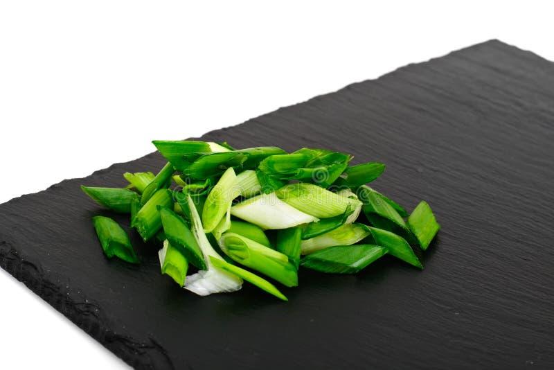 Зеленый лук-порей на черной плите стоковое фото