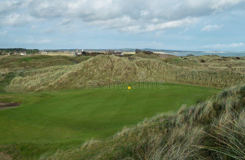 Зеленый цвет гольфа связей tucked между песчанными дюнами стоковая фотография rf