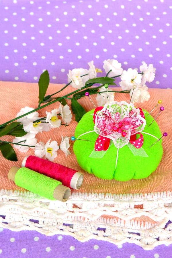 Зеленый pincushion с серией штырей для шить стоковые изображения
