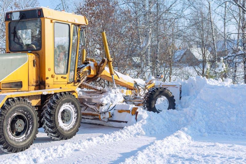 Зима, бульдозер очищает снег на дороге стоковое фото rf
