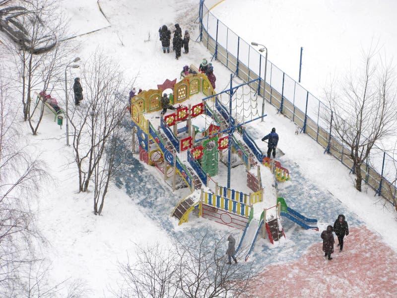 Зима, городской двор, спортивная площадка детей, люди стоковое фото rf