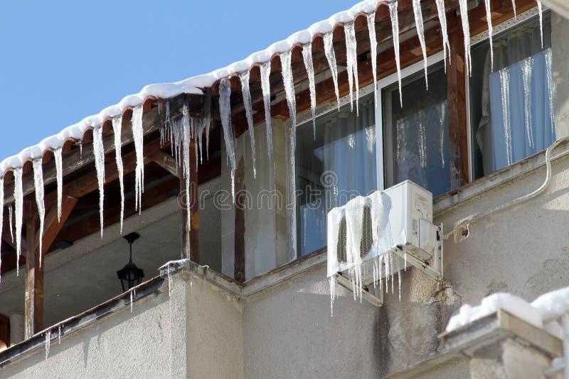 Зима Огромные опасные сосульки льда висят над здоровьем угрозой улицы и жизнью людей вися от крыши здания стоковое изображение rf