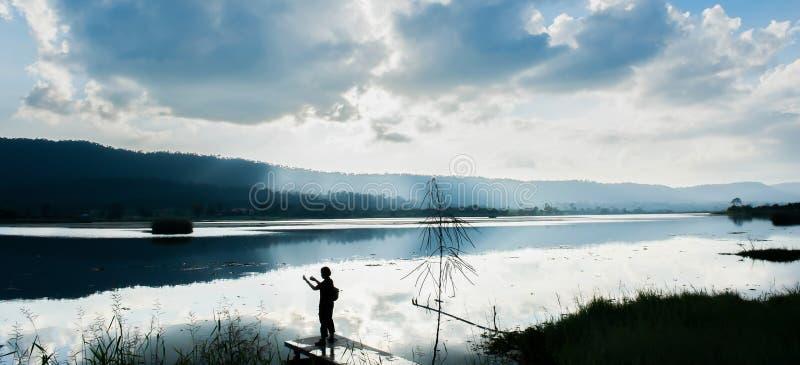 Зима озером, положение женщины путешественника на террасе и наслаждаться виде на озеро с камерой на заходе солнца, яркие облака и стоковые изображения rf